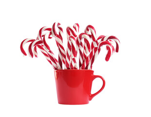 Many sweet candy canes in red cup on white background. Christmas treat