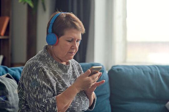 New life of favorite book. Senior woman enjoying audiobook in headphones, free space.