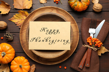 Seasonal table setting with Happy Thanksgiving Day card and pumpkins on wooden table, flat lay