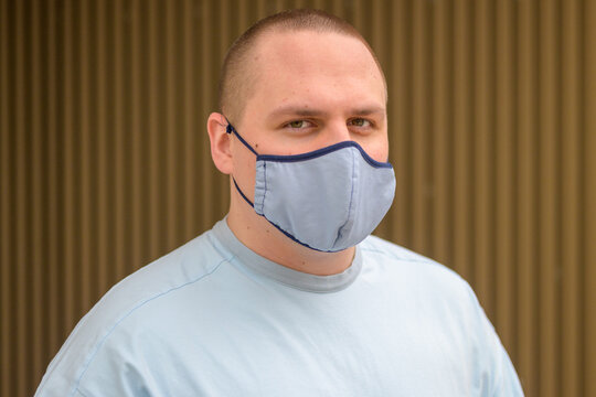 Thoughtful young man wearing a textile face mask