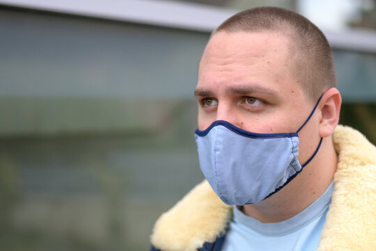 Young man in a washable blue cloth face mask