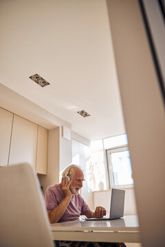 Male pensioner looking fixedly at his laptop