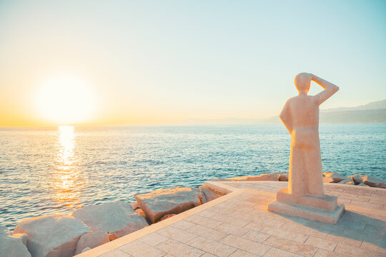 POSTIRA, CROATIA - JULY 12, 2017: Famous monument of person looking into a horizon in a small town Postira - Croatia, Brac island
