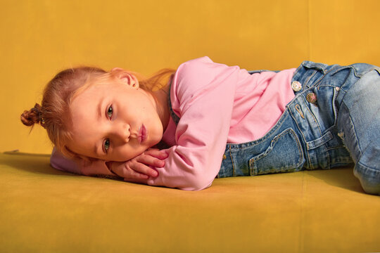 Lifestyle of american or european kid girl. Smiling girl at home lying on a couch. Concept of children life
