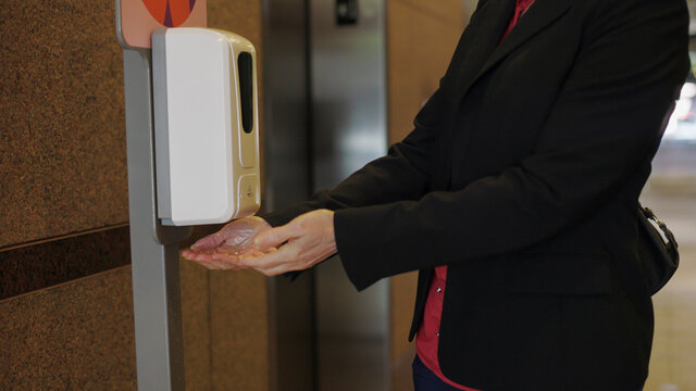 woman using a hand sanitizer station in an office building during covid.
