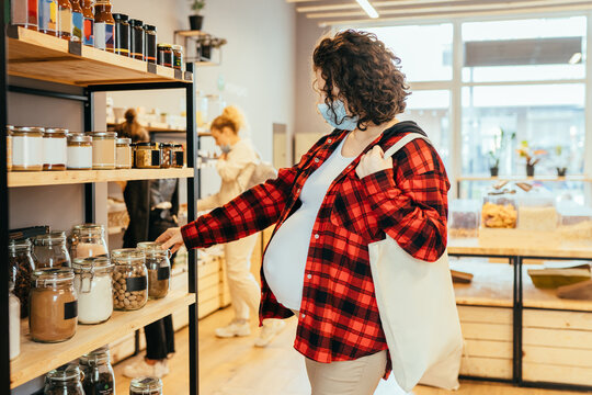 Pregnant woman with a cotton shopping bag wearing a protective face mask choosing foods in a plastic free grocery store. Sustainable shopping at small local businesses.
