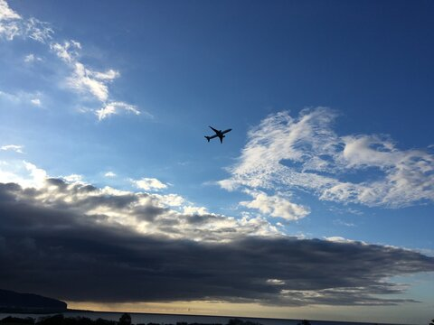 Flying airplane over blue cloudy sky