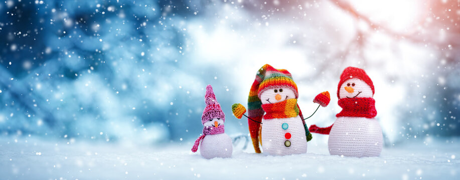 Little knitted snowmen on soft snow on blue background