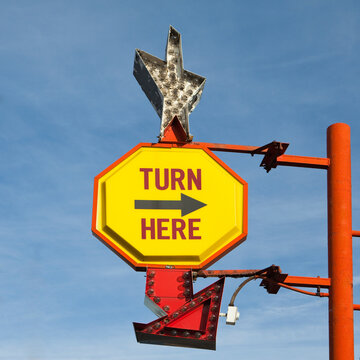 Turn Here, yellow traffic sign with arrow, on a gantry with a silver star shape