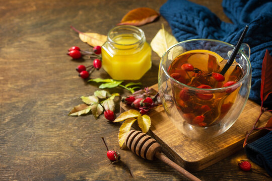 Healthy winter vitamin drink. Hot rosehip tea with honey and dried fruits on a wooden table top. Copy space.