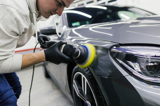 Car detailing - Worker with orbital polisher in auto repair shop.