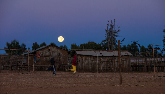 The moon sets over a remote Ethiopian village as two people run by.