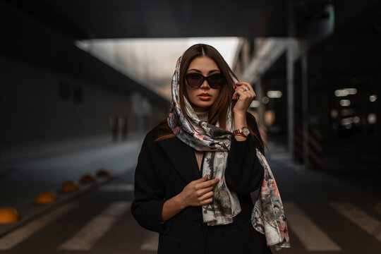 Luxurious attractive young woman with sexy lips with stylish silk scarf on head in trendy black coat in fashionable sunglasses posing on the road in the city. Elegant urban girl fashion model outdoors