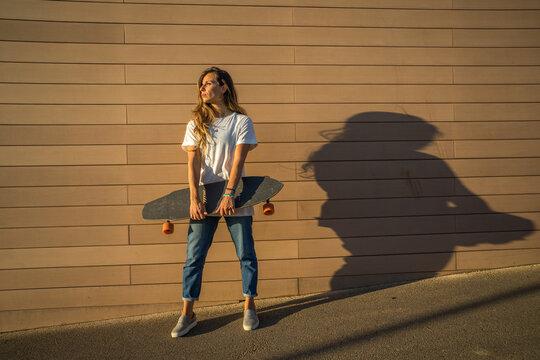 mujer con vaqueros y camiseta blanca posando con un skate