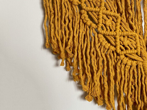close up yellow macrame wall hanging on white wall