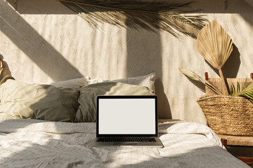Blank screen laptop in bed with pillows and linens. Boho style home interior design with warm sunlight shadows on the wall. Copy space mockup template. Freelancer, blogger work business concept.