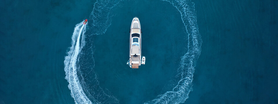 Aerial drone ultra wide top down photo of stunt man performing extreme stunts and circling with jet ski watercraft over anchored yacht in deep blue ocean at dusk