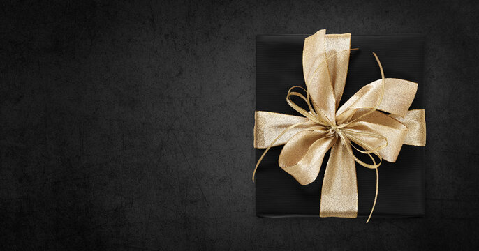 Black Friday gift package wrapped with golden ribbon bow isolated on black background, template for promotional card with copy space