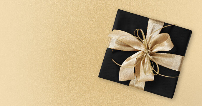 Black Friday gift package wrapped with golden ribbon bow isolated on golden background, template for promotional card with copy space