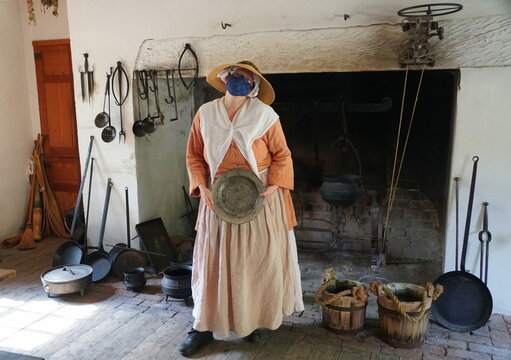 Williamsburg, Virginia, U.S.A - June 30, 2020 - A lady inside a kitchen wearing a mask as required during a tour