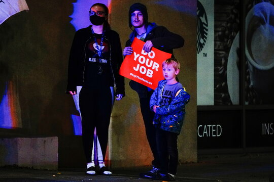 """Supporters of U.S. President Donald Trump and their child watch as other Trump supporters argue with Black Lives Matter (BLM) counterprotesters at a a """"Stop the Steal"""" protest outside Milwaukee Central Count, in Milwaukee"""