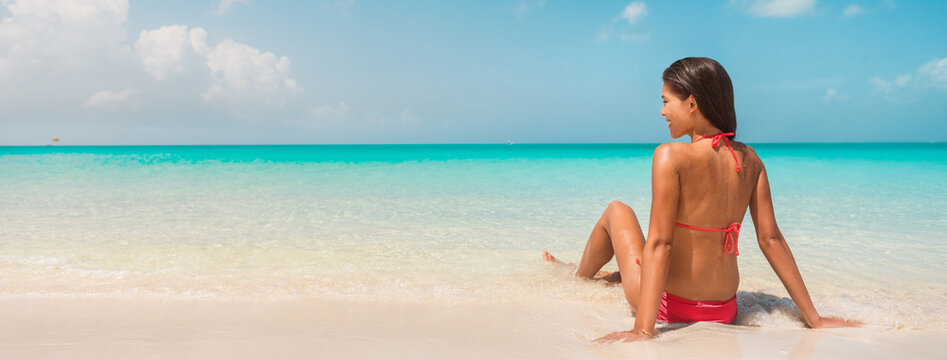 Beach vacation banner panorama background of bikini woman relaxing in water sun tanning on Caribbean island. Winter south holidays.