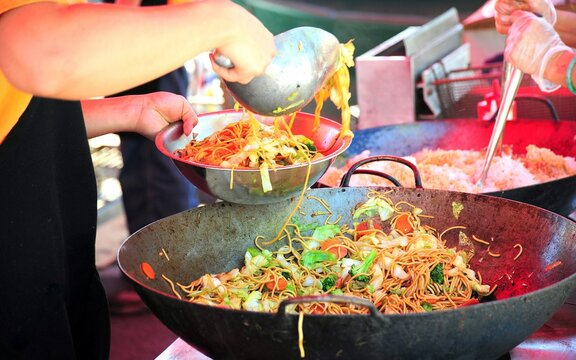Chinese chicken lo mein cooked in a wok outdoors.