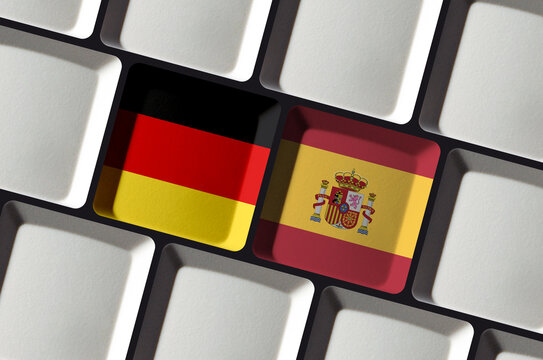 Keyboard with German Germany and Spanish Spain flag - concept online language school learning, translation or bilateral partnership
