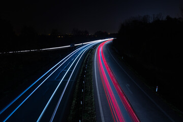 Vehicle car light trails on highway in red and white color. Trafic at night, toned long exposure