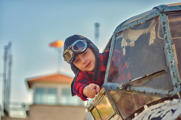 Portrait of a happy boy in a flying retro helmet in the cockpit of an old plane