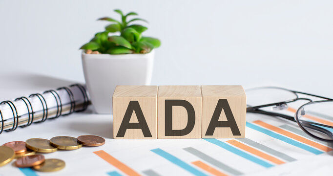 ADA word on wood blocks concept with chart, coins, notebook and glasses.