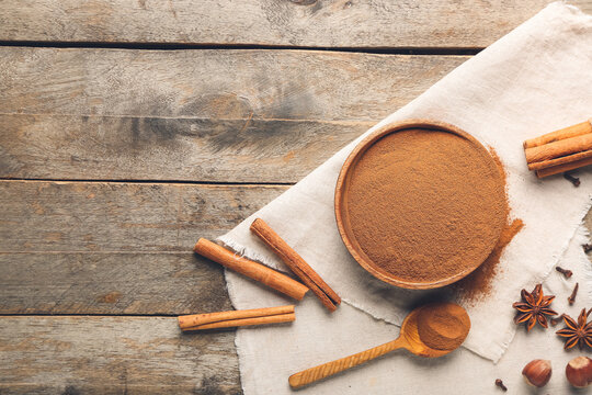 Bowl and spoon with cinnamon powder on wooden background