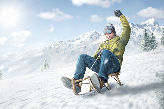Happy man riding on a sled in winter