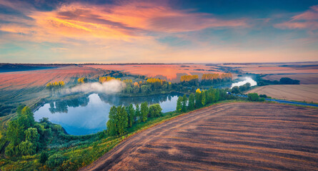 Stunning summer sunrise on Ternopil outskirts with two lakes and asphalt road on the midle. Foggy morning view of hte Ukrainian countryside. Wonderful landscape of field of wheat.