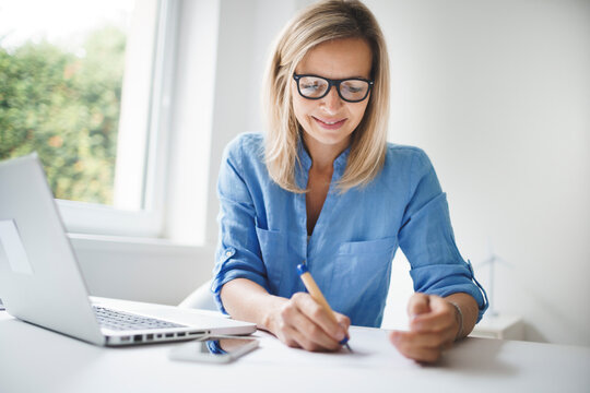 young and blond business woman with blue shirt and glasses is working in office and is happy