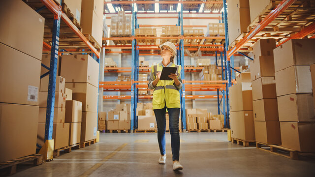 Professional Female Worker Wearing Hard Hat Checks Stock and Inventory with Digital Tablet Computer Walks in the Retail Warehouse full of Shelves with Goods. Working in Delivery, Distribution Center