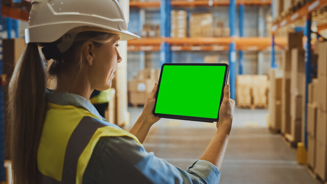 Professional Female Worker Wearing Hard Hat Uses Digital Tablet Computer with Green Chroma Key Screen in Landscape Mode in the Retail Warehouse full of Shelves with Goods. Over the Shoulder view