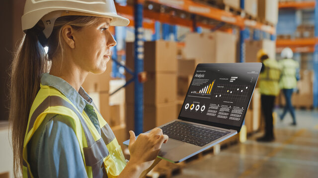 Professional Female Worker Wearing Hard Hat Holds Laptop Computer with Screen Showing Analysis Software in the Retail Warehouse full of Shelves with Goods. Over the Shoulder Side View