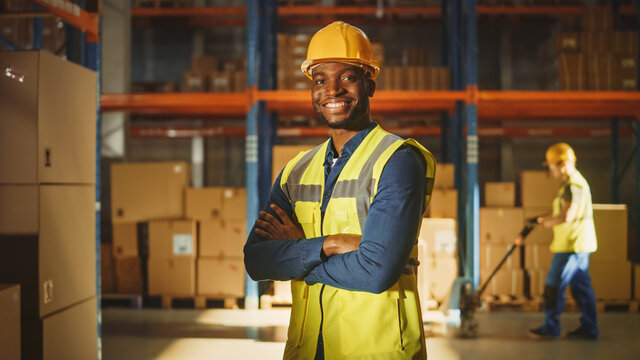 Handsome and Happy Professional Worker Wearing Safety Vest and Hard Hat Smiling with Crossed Arms on Camera. In the Background Big Warehouse with Shelves full of Delivery Goods. Medium Portrait