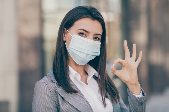 Photo of beautiful businessperson show okay sign wear medical mask formalwear suit blazer outside in outdoors