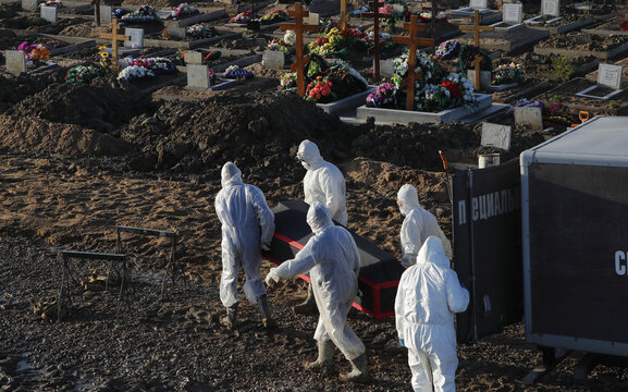 Grave diggers bury a person at a graveyard in Saint Petersburg