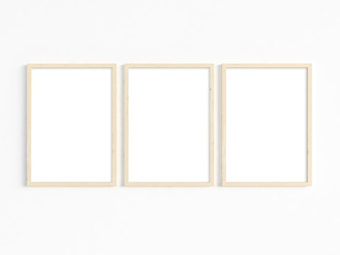 A mockup of three thin A4 wooden frames with portrait orientation. 3D illustration.