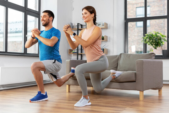 sport, fitness, lifestyle and people concept - smiling man and woman exercising and doing squats in low lunge at home