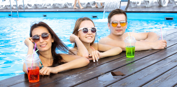 Happy friends enjoying in pool bar. Summer beach party. Drinking tropical alcohol cocktails.