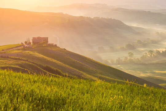 House on a hill in the dawn mist