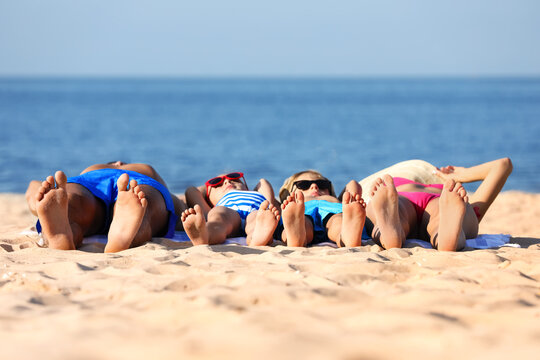 Family lying on sandy beach near sea. Summer holidays