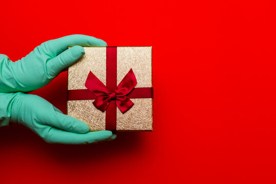 Gift box, hands in medical gloves. Preparation for the holiday during the coronavirus pandemic.
