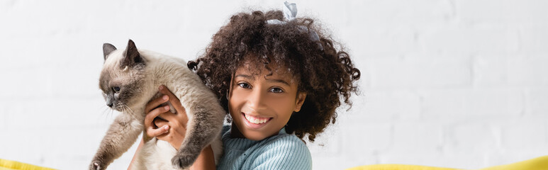 Cheerful african american girl holding siamese cat, while looking at camera at home, banner