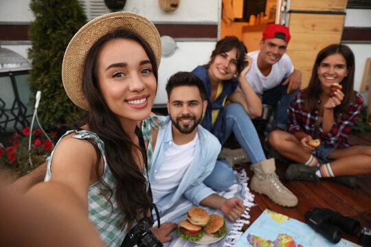 Happy friends taking selfie near motorhome. Camping season