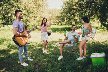 Photo of brown haired happy cheerful friend play guitar dance talk drink beer weekend outside in backyard outdoors Wall mural